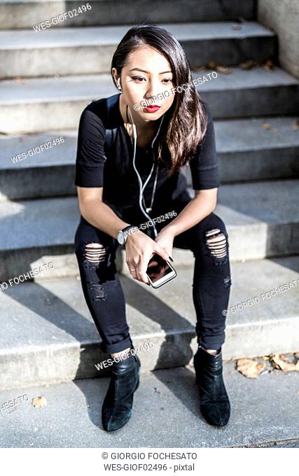 Portrait of young woman dressed in black sitting on steps listening music with earphones and cell phone