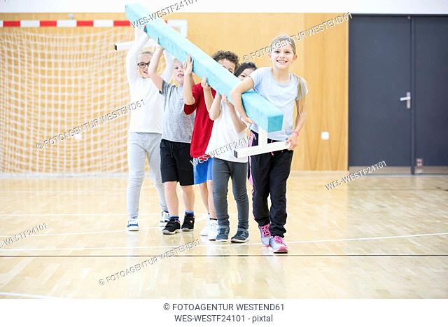 Pupils carrying balance beam in gym class