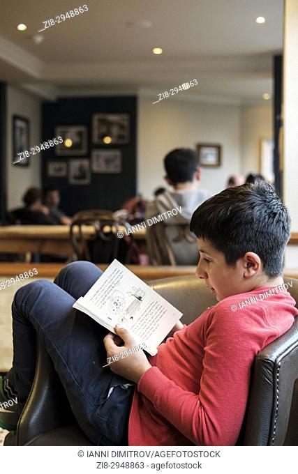 Boy,10 years old reads book in library,UK