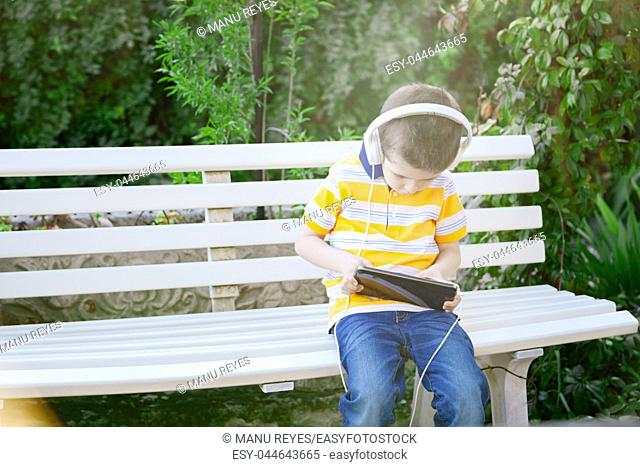 boy listening to music with withe headphones on the outside