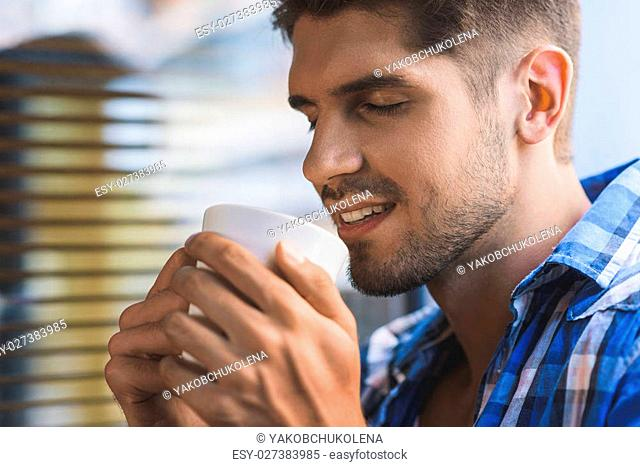 freelancer enjoying of coffee smell with closed eyes