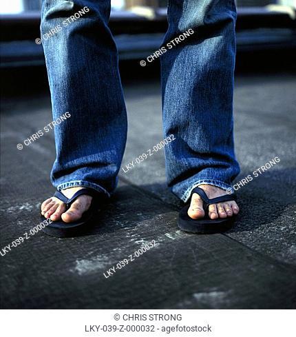 Man's feet wearing flipflop sandals