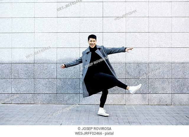 Stylish young man dancing on the street