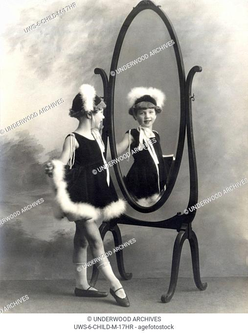 San Francisco, California: c. 1905.A young girl admires her outfit in a mirror