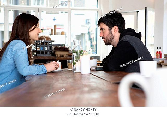 Mid adult couple sitting at cafe table with coffee, chatting