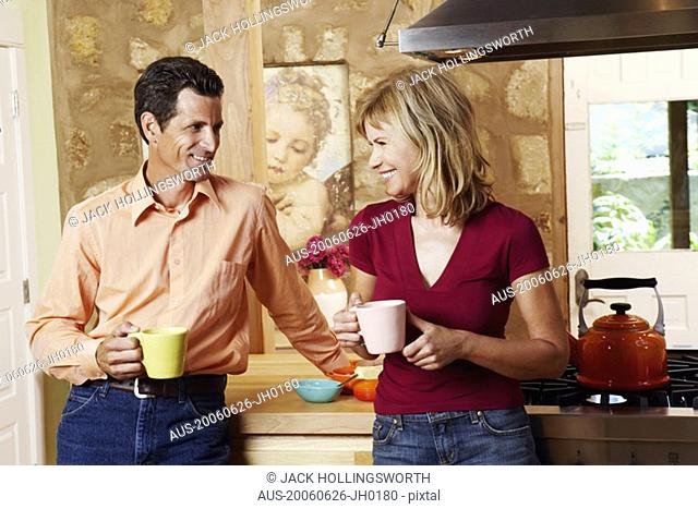 Mature couple smiling and holding cups