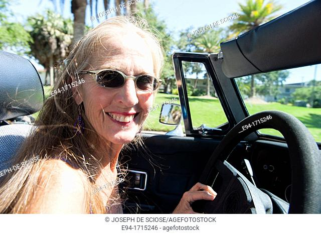 57 year old woman with long hair blowing in her face driving her MG convertible car