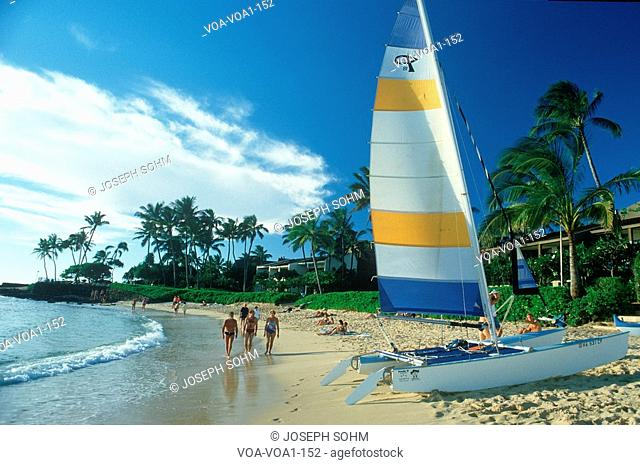 Tourists walking on the beach at a resort hotel on Hanapepe Bay in Kauai, Hawaii