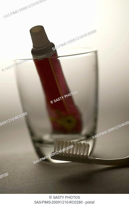Close-up of a toothbrush and a toothpaste in a glass