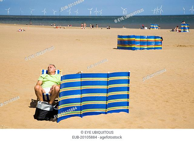 Man sleeps in sunshine behind striped windbreak with Lincs Wind Farm offshore behind