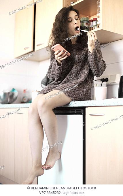 young woman tasting spoon of coffee in kitchen at home, morning