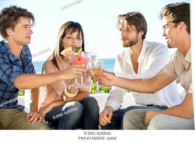 Group of friends toasting drinks outdoors on vacation