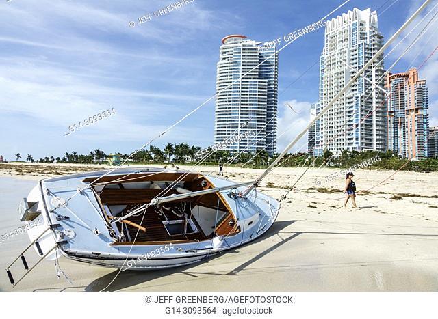 Florida, Miami Beach, Hurricane Irma, damage, beached grounded damaged sailboat, luxury high-rise buildings, sand, woman, walking