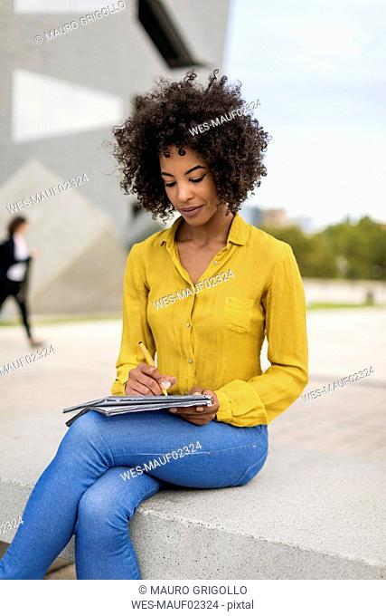 Woman sitting on bench taking notes