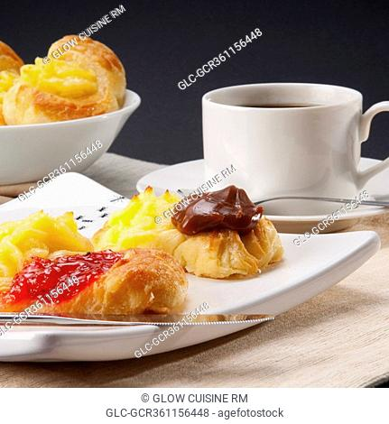 Close-up of danish pastries served with a cup of black coffee