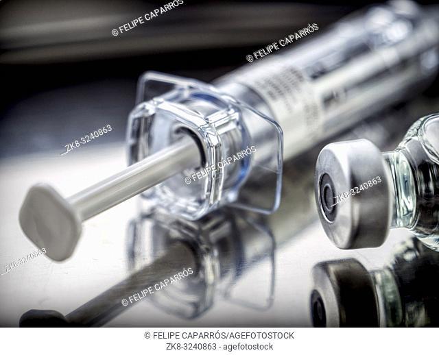Syringe vintage next to vials, conceptual image