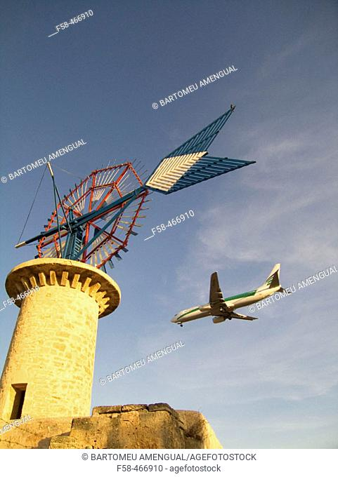 Windmill and airplane landing. Son Sant Joan airport. Palma de Mallorca. Balearic Islands. Spain