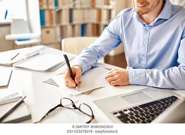 Smiling businessman writing down his ideas on paper at workplace