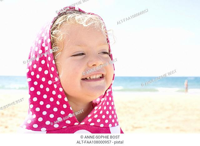 Girl wearing hood with polka dots at beach