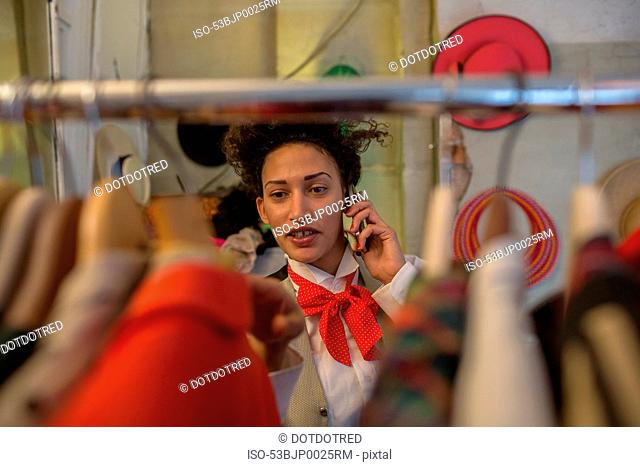 Woman on cell phone in clothes shop