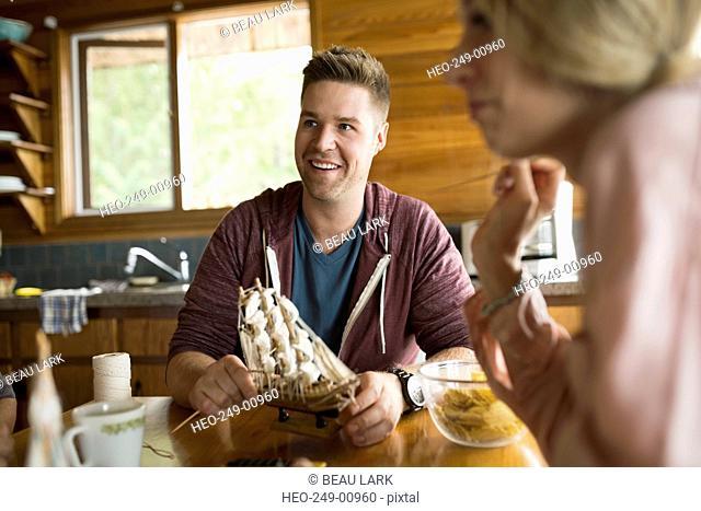 Smiling man holding model ship at table