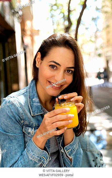Young woman holding glass with fresh juice
