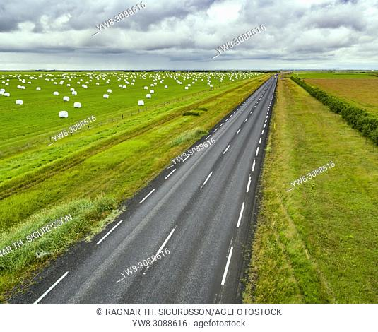 Hay bales and empty road, summertime, South Coast, Iceland