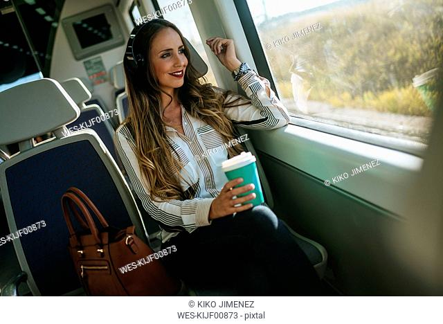 Woman on a train listening to music with headphones and drinking coffee