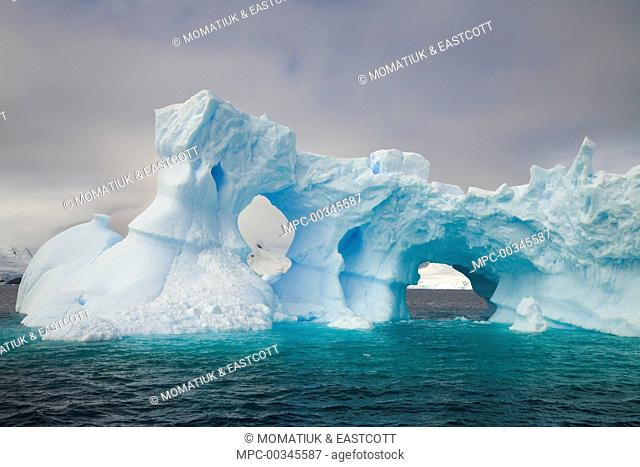 Iceberg with arches and turrets sculpted by waves and melting of ice, Gerlache Passage, Antarctica