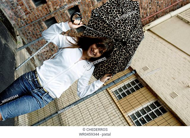 Portrait of a young woman holding an umbrella and smiling