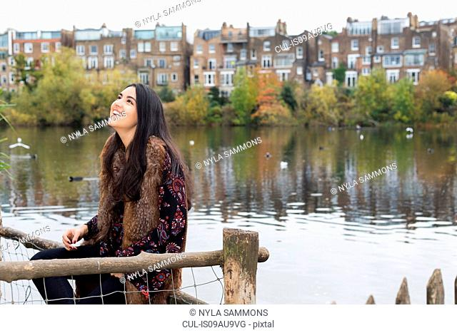 Young woman relaxing by lake, Hampstead Heath, London