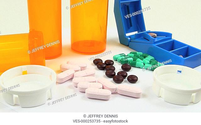 Capsules, pills, tablets and pill splitter rotate into view clockwise while on white table with empty medicine bottles and caps