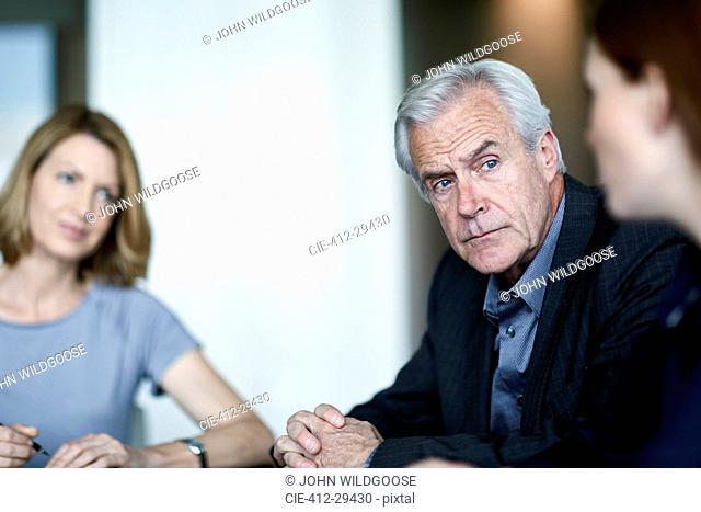 Serious senior businessman listening to businesswoman in meeting