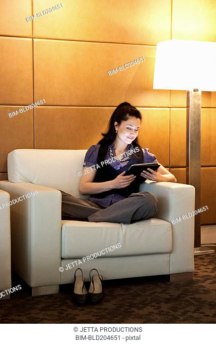 Mixed race businesswoman using tablet computer
