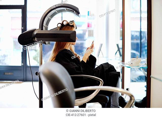 Woman sitting under dryer texting with cell phone in hair salon