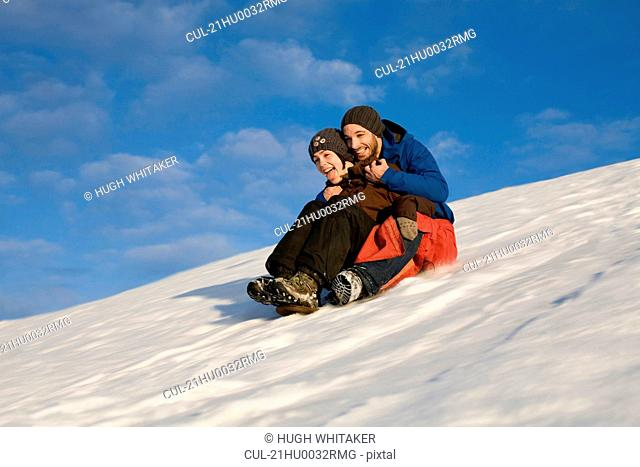 Couple sliding down snowy hill