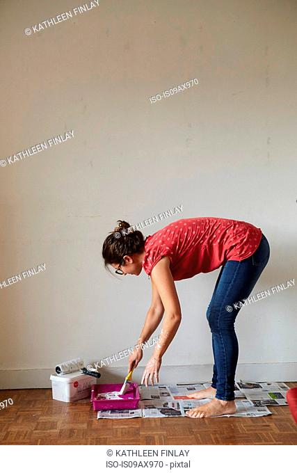 Woman standing in front of wall, dipping paintbrush into paint