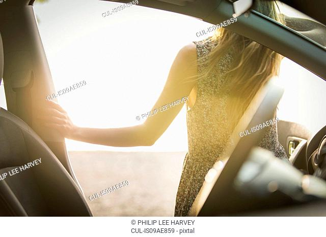 Young woman getting out of car