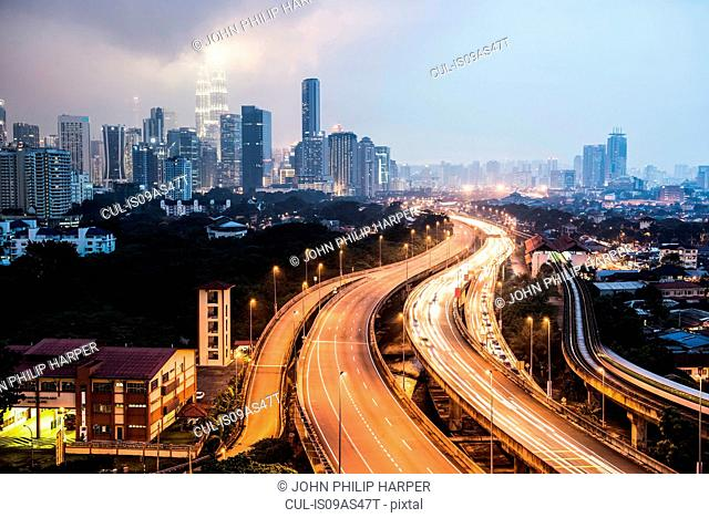 Highway with light trails and skyline at dusk, Kuala Lumpur, Malaysia