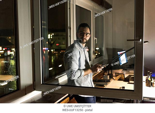 Portrait of businessman working late in office