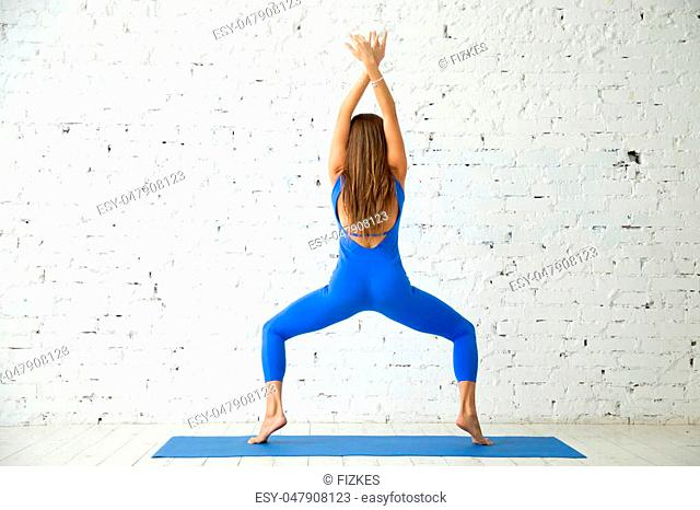 Young attractive woman practicing yoga, standing in Goddess exercise, Sumo Squat pose, working out, wearing sportswear, blue jumpsuit, indoor full length
