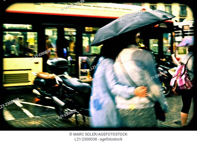 Couple under an umbrella on a rainy day. In the background a bus passes. Barcelona, Catalonia, Spain
