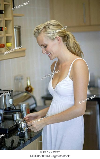 Young woman in the white dress is preparing espresso in the kitchen