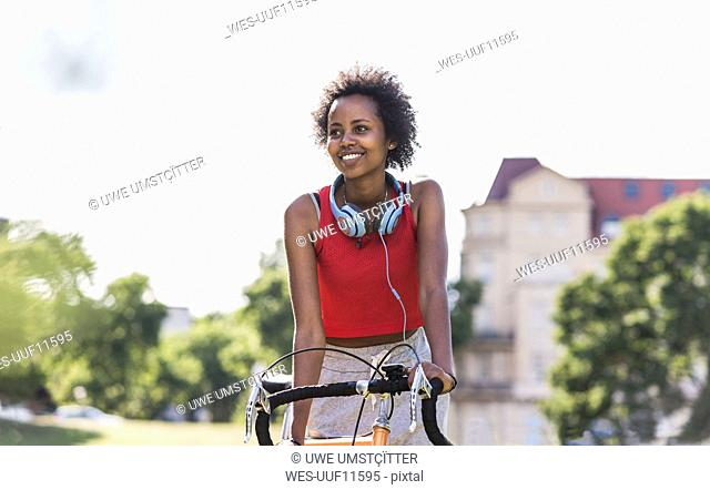 Smiling sporty young woman on bicycle in park