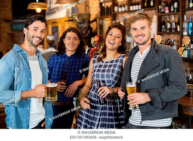 Portrait of friends holding beer glasses and bottles in pub