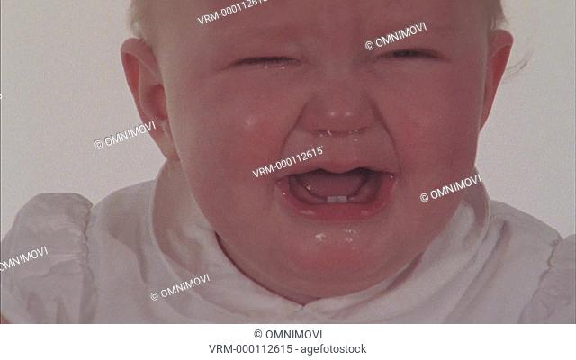 Baby boy crying, person's hand wiping nose