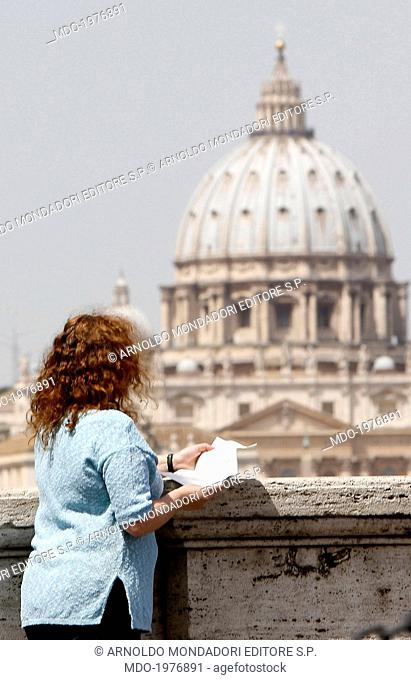 Woman reading a letter. In the background the St. Peter's Basilica. Rome, Italy. 22nd May 2014