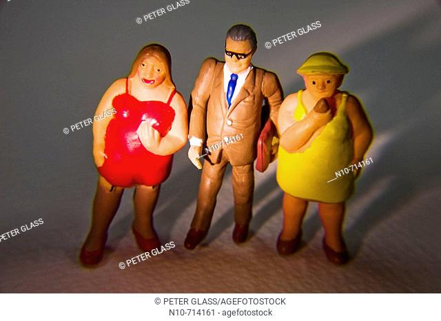 Plastic figures of a man,wearing glasses and holding a satchel, standing between two heavy women