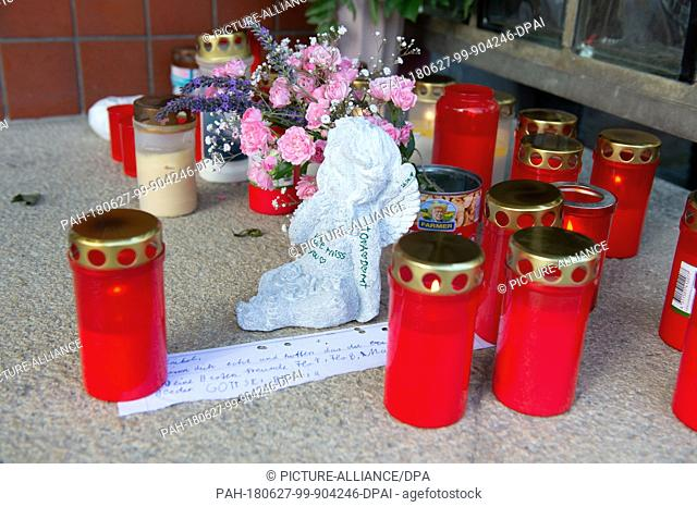 27 June 2018, Germany, Gunzenhausen: Mourning candles, flowers, an angel figurine and a farewell letter, standing at the entrance of a high-rise building