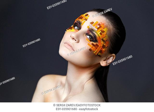Portrait of a girl with an original make-up. Beauty close-up. Orange and red rhinestones on a face